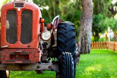 An old red tractor near a farm field. royalty free stock image