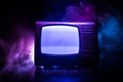 Old vintage red TV with white noise on dark toned foggy background. Retro old Television reciever no signal. Selective focus royalty free stock photo