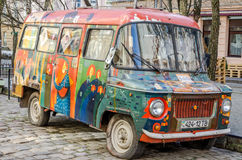 Old vintage retro abandoned car painted graffiti artists in the hippy style is broken on one of the streets of Lviv Royalty Free Stock Photo