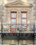 Old vintage retro balcony with columns and ornaments on an old building with windows on one of the streets of Lviv, Ukraine. Old vintage retro balcony with Royalty Free Stock Image