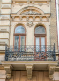 Old vintage retro balcony with columns and ornaments on an old building with windows on one of the streets of Lviv, Ukraine. Old vintage retro balcony with Stock Photos