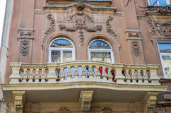 Old vintage retro balcony with columns and ornaments on an old building with windows on one of the streets of Lviv, Ukraine. Old vintage retro balcony with Royalty Free Stock Photography
