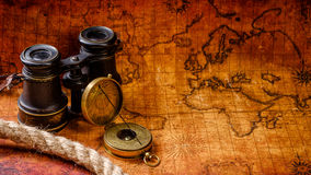 Old vintage retro compass and spyglass on ancient world map. Old vintage retro compass and binoculars on ancient world map. Vintage still life. Travel geography Stock Images