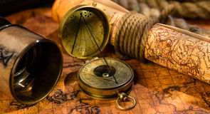 Old vintage retro compass and spyglass on ancient world map. Vintage still life. Travel geography navigation concept background Royalty Free Stock Images