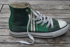 Old vintage retro green striped canvas sneaker Royalty Free Stock Photo