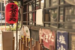 Old vintage retro japanese metal signs and red rice paper lantern where it is written 'Oshokujidokoro' which means 'Meal' on. Old vintage retro japanese metal stock image