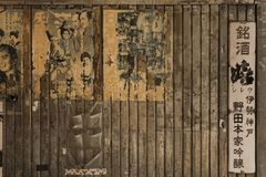 Old vintage retro japanese samurai movie posters and rusty metal. Advertising sign of old sake brand on underpass Yurakucho Concourse wall under the railway stock photography