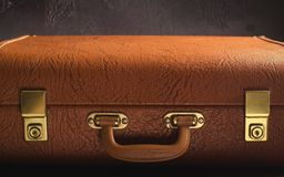 Old vintage, retro leather suitcase on dark background. Front view, toned Royalty Free Stock Photo