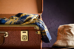 Old vintage, retro open suitcase with hats and checkered shirt on dark background. Travel concept Stock Photos