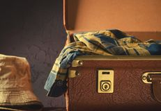 Old vintage, retro open suitcase with hats and checkered shirt on dark background. Travel concept Stock Photography