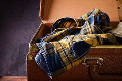 Old vintage, retro open suitcase with man`s checkered shirt on dark background. Travel concept Stock Image