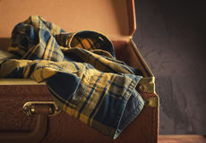 Old vintage, retro open suitcase with man`s checkered shirt on dark background. Travel concept. Toned Royalty Free Stock Photography