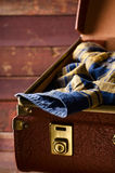 Old vintage, retro open suitcase with man`s checkered shirt on dark background. Travel concept. Vertical Royalty Free Stock Photography