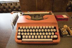 Old vintage Retro orange typewriter. On table Royalty Free Stock Photos