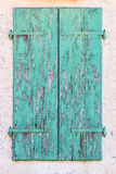 Old vintage retro wooden turquoise cracked paint window blinds,. Shutter on white stone wall as historic architecture background Royalty Free Stock Photo