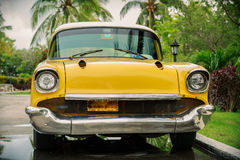 Old, vintage, retro, yellow beautiful classic car. Front view of old, vintage, retro, yellow beautiful classic car, on natural overcast rainy warm day standing Royalty Free Stock Images