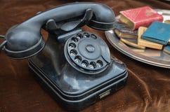 Old vintage rotary dial black telephone on brown velvet. Sheet Stock Photos