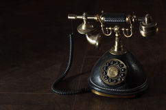 Old vintage rotary phone. Old vintage or antique rotary phone with a handset and cradle on a dark shadowed background with copyspace royalty free stock photography