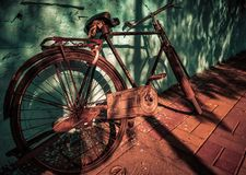 old vintage rustic metallic bicycle with blue wall as a background with light and shadow can be used as a advertising stock image