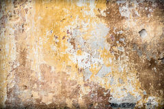 Old vintage rustic wall with cracked paint layers. As an aging ruin background Royalty Free Stock Image