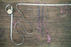 Old vintage rusty measuring tape on grunge wooden background Royalty Free Stock Photo
