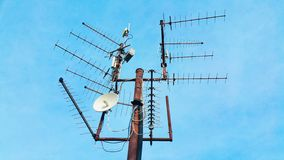 Old vintage rusty television mast with many antennas pointing to different direction catching television signal waves on a blue sk. Y background royalty free stock image