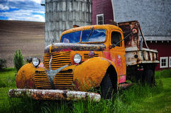Old vintage scrapped truck in front of a red barn