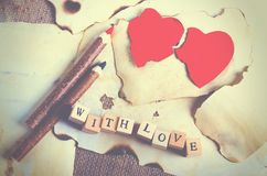 Old vintage sheet of paper, two red hearts, wooden pencils and words With love on cubes on burlap, sackcloth background. Retro design effects Royalty Free Stock Images