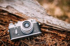 Old Vintage Small-Format Rangefinder Camera, 1950-1960s. 35mm Vintage Old Retro Small-Format Rangefinder Camera On Old Fallen Wood Tree In Forest Stock Photo