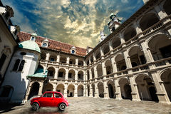 Old vintage small red car in historical scene. Klagenfurt ancient building Stock Photography