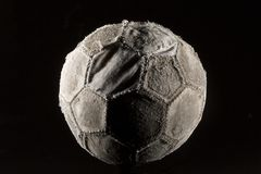 Old and vintage soccer ballon. On black background Royalty Free Stock Image