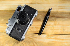 Old vintage soviet rangefinder camera and fountain pen Royalty Free Stock Photo