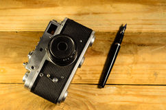 Old vintage soviet rangefinder camera and fountain pen Stock Photography