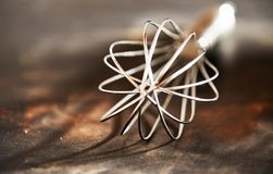 Old vintage steel wire whisk on a kitchen table. Old vintage steel wire whisk on a rustic wooden kitchen table in a close up view to the end royalty free stock photos