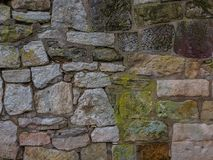 The old and vintage stone wall in a city.  Royalty Free Stock Images