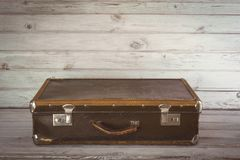 Old vintage suitcase in the room on wooden light board. Close up Stock Images