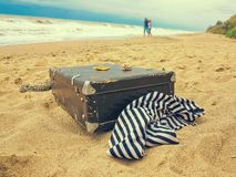Old vintage suitcase for travel and family vacations lies on the beach. Man and woman in love Sea shore ocean. Photo in a trendy royalty free stock images