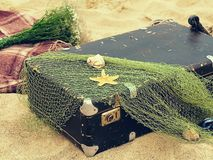 Old vintage suitcase for travel and family vacations lies on the beach. Sea shore ocean. Photo in a trendy retro style royalty free stock image