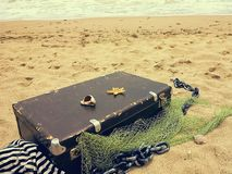 Old vintage suitcase for travel and family vacations lies on the beach. Sea shore ocean. Photo in a trendy retro style stock image