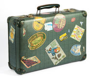 Old vintage suitcase with travel labels. Old vintage suitcase covered with colorful travel labels depicting a range of international tourist destinations Stock Photos
