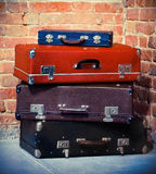 Old vintage suitcases isolated near brick wall. Luggage Stock Photo