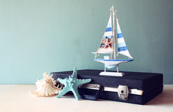 Old Vintage sutcase with toy boat' starfish and seashell on wooden board. travel and voyage concept. retro filtered image. Royalty Free Stock Images