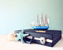 Old Vintage sutcase with toy boat' starfish and seashell on wooden board. travel and voyage concept. retro filtered image Stock Photo