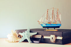 Old Vintage sutcase with toy boat' starfish and seashell on wooden board. travel and voyage concept. retro filtered image. Stock Photography