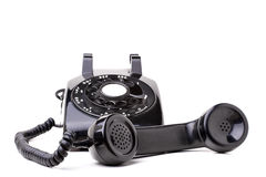 Old Vintage Telephone. An old black vintage rotary style telephone off the hook isolated over a white background Stock Photo