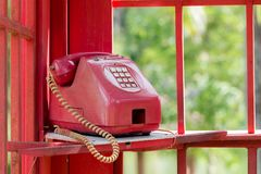 Old vintage telephone or phone in red box. Stock Photos