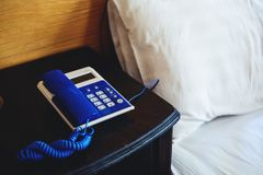 Old vintage telephone on side bed table in bedroom Stock Image