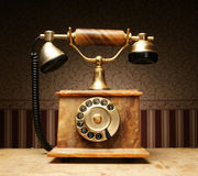 An old vintage telephone standing on a table Stock Image
