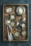 Old vintage tin baking molds and cutlery in wooden tray Royalty Free Stock Photos