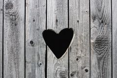 Old vintage rural toilet door with a heart shaped hole in the wooden shutters background Stock Photo
